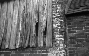 Black and white photograph taken with voigtlander vito 1 film camera of a close up detail of brick and weathered old wood shiplap