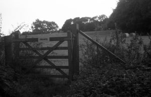A black and white photograph taken with voigtlander vito 1 film camera of a private sign on a gate to a field