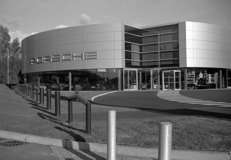 Black and white photograph of a Porsche Dealership by Darron Barnes